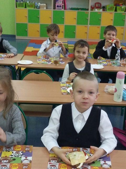Uczniowie jedzą kanapki i sałatki